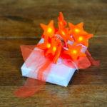 Pacchetti di Natale: carta bianca e stelle luminose