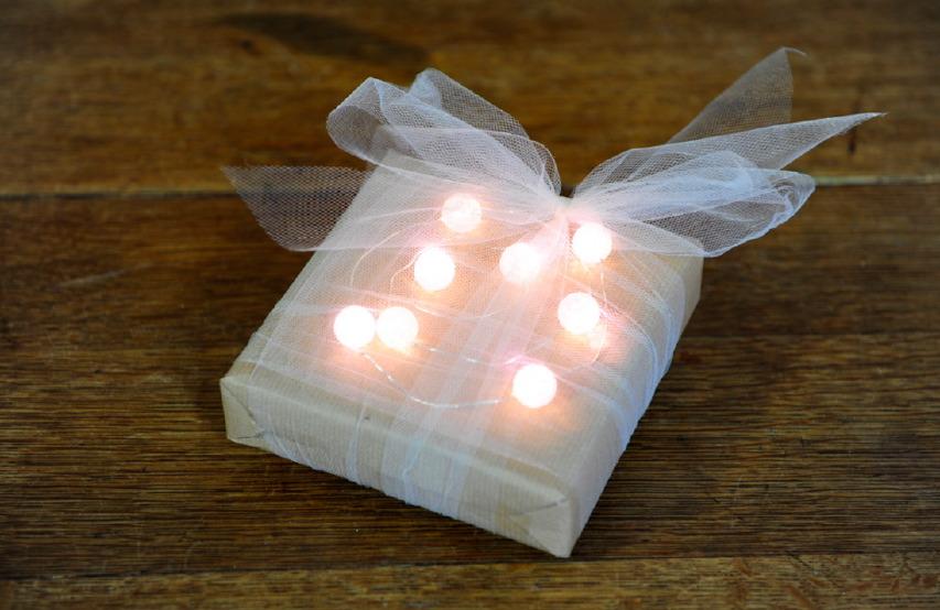 Pacchetto di Natale con carta da pacchi grezza e palline luminose