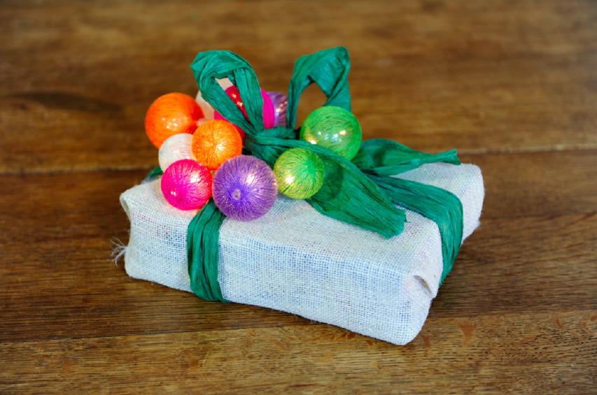 Un pacchetto di Natale con palline colorate luminose juta