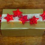 Pacchetto di Natale con carta regalo, nastro di juta e stelle luminose