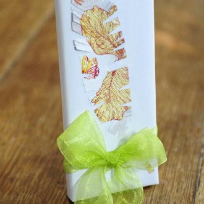 """Pacchetto di Natale con fiocco e piuma di carta. <a href=""""http://www.comefareconbarbara.it/trasformare-un-pacchetto-anonimo-un-pacchetto-originale/""""><strong><u>Ecco il video tutorial</a></u></strong>"""