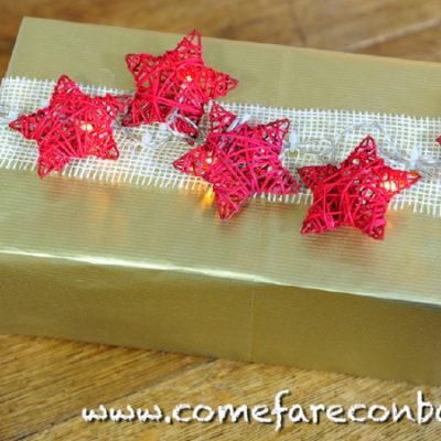 """Un pacchetto di Natale con una catena di stelle luminose. <a href=""""http://www.comefareconbarbara.it/5-idee-luminose-per-i-vostri-pacchetti-regalo-di-natale/""""><strong><u>Le cinque idee per pacchetti luminosi le trovi tutte qui, in questo video tutorial</a></strong><u>."""