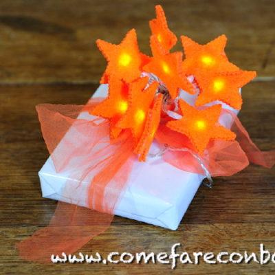 """Un pacchetto di Natale con stelline luminose raccolte a """"mazzo di fiori"""". <a href=""""http://www.comefareconbarbara.it/5-idee-luminose-per-i-vostri-pacchetti-regalo-di-natale/""""><strong><u>Le cinque idee per pacchetti luminosi le trovi tutte qui, in questo video tutorial</a></strong><u>."""